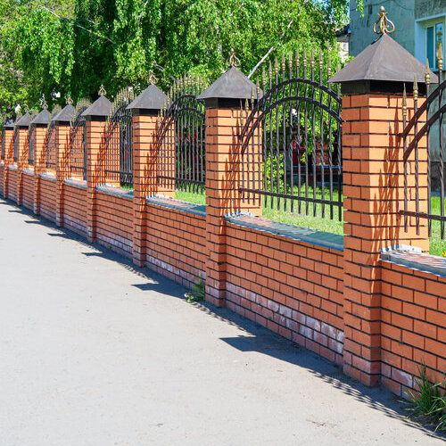 Metal fence with red brick columns.