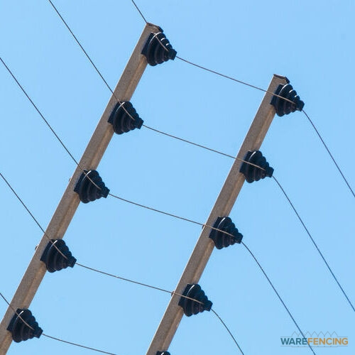 Close up wall mounted high voltage electric security fence instalation isolated against blue sky background